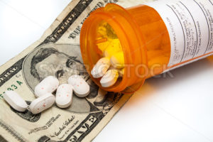 Bottle of prescription pills laying on money - Stock Images 4 You