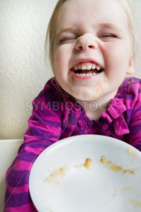 Child finished with her bowl of healthy food and a messy face - Stock Images 4 You