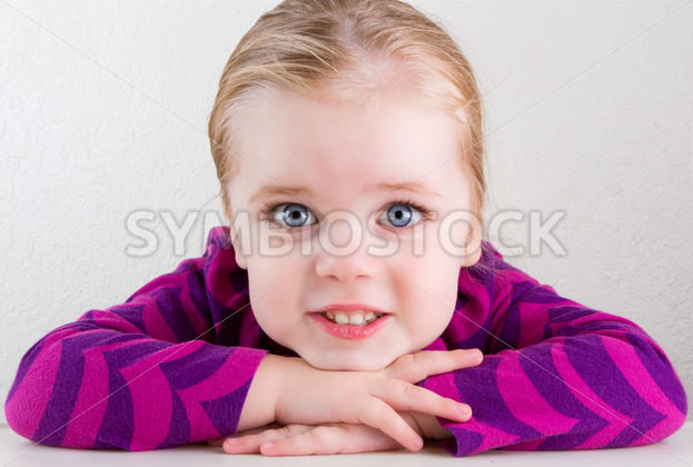 Child resting her head on her hands smiling – Stock Images 4 You