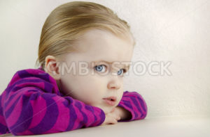 Cute  young girl resting her head on a table. - Stock Images 4 You