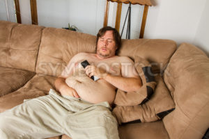 Fat guy sleeping on the couch - Stock Images 4 You