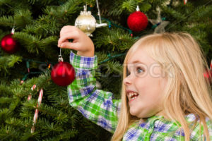 Girl is putting her ornament on the tree - Stock Images 4 You