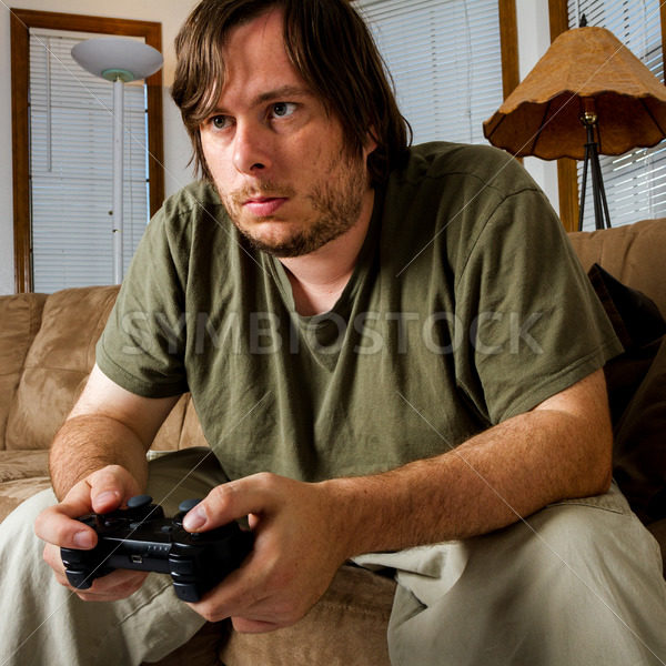 Middle aged man playing games on the couch – Stock Images 4 You