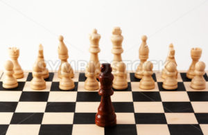 Single chess piece standing up against a collection of different pieces - Stock Images 4 You