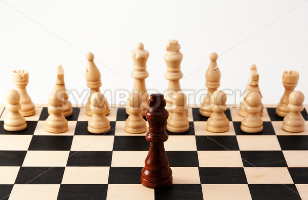 Single chess piece standing up against a collection of different pieces – Stock Images 4 You
