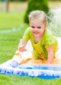 Smiling girl cooling off on a hot summer day - Stock Images 4 You