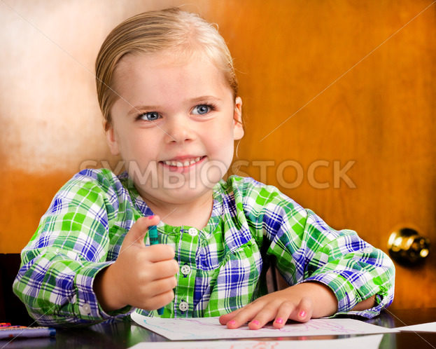 Smiling young girl doing a drawing. – Stock Images 4 You