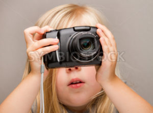 Young child holding a camera taking a picture - Stock Images 4 You