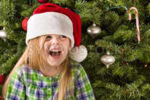 Young girl smiling wearing a santa hat - Stock Images 4 You