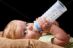 Young little baby drinking from his bottle - Stock Images 4 You