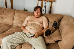 fat guy laying on the couch  - Stock Images 4 You