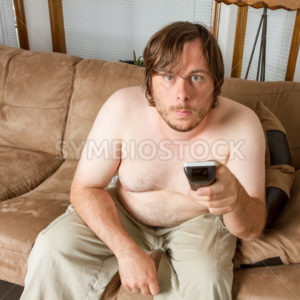 young man sitting on the couch working the TV - Stock Images 4 You