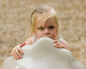 Child hiding behind a object at the playground - Stock Images 4 You