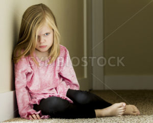 Child laying up against a wall with a very sad look on her face - Stock Images 4 You