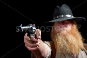 Cowboy holding his pistol up for the shot with his finger on the trigger - Stock Images 4 You