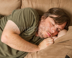 Fat guy asleep on the couch - Stock Images 4 You