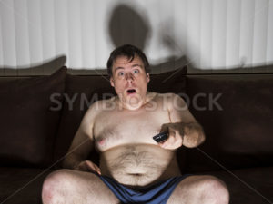 Fat man shocked while watching TV - Stock Images 4 You