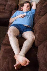 Man laying down on the couch - Stock Images 4 You