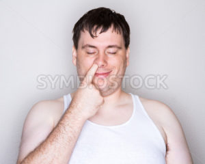 Man picking his nose with a white shirt on - Stock Images 4 You