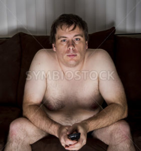Obese naked man watching TV - Stock Images 4 You
