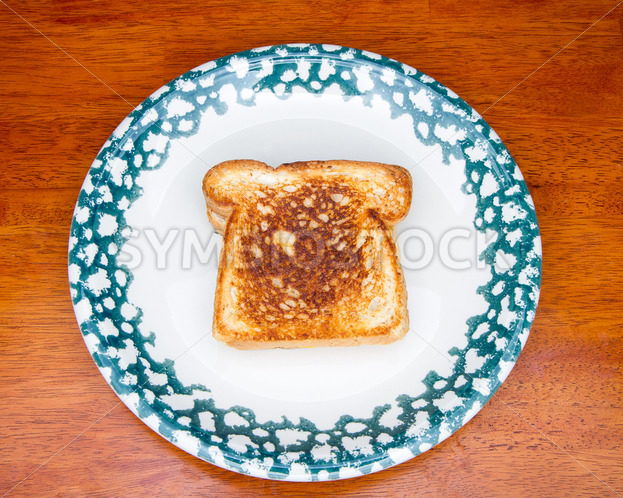 Piece of toast on a decorative plate – Stock Images 4 You