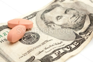 Two pills sitting on a five dollar bill - Stock Images 4 You